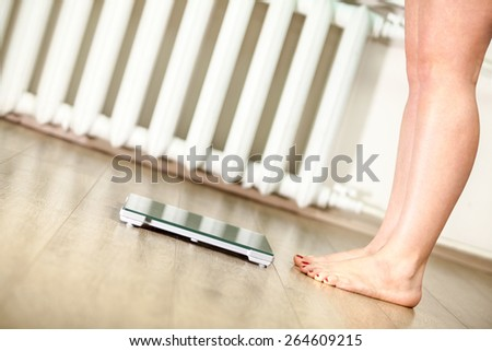 Caucasian woman with bare feet is in front of floor weight scales - stock photo