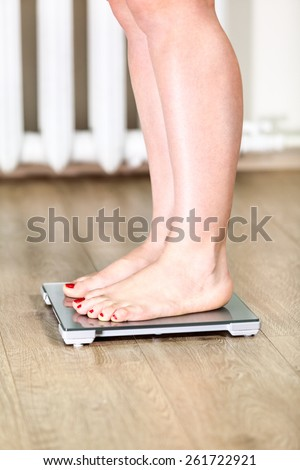 Caucasian woman with bare feet is on floor weight scales - stock photo