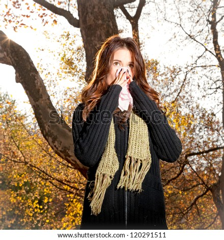 Caucasian woman with cold sneezing into tissue in autumn park