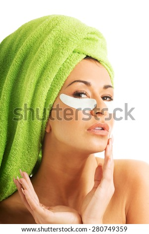 Caucasian woman with gel eye mask and hands on chin - stock photo