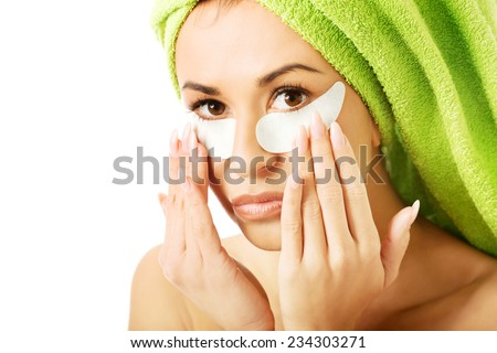 Caucasian woman with gel eye mask touching face. - stock photo