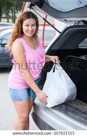 Caucasian woman with shopping bag loading her suv - stock photo