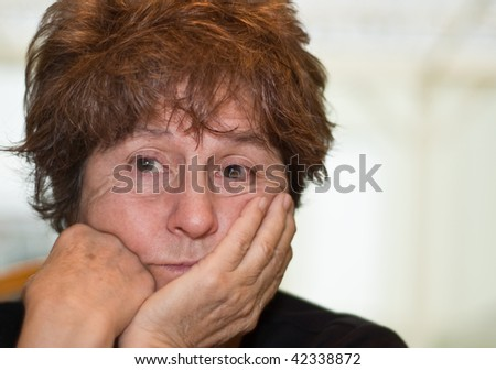 Caucasian woman worried and contemplating posed in front of white background - stock photo