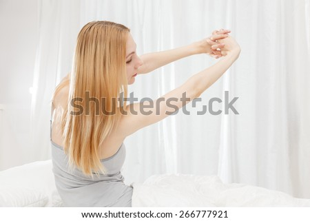 Caucasian women to stretch on the bed - stock photo