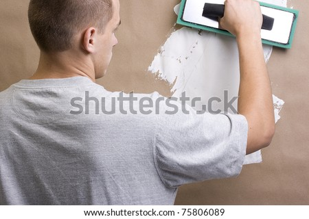 Caucasian worker plastering a brown wall with white plaster. - stock photo