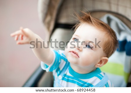 caucasian 1 year old boy sitting in baby carriage and pointing finger on something