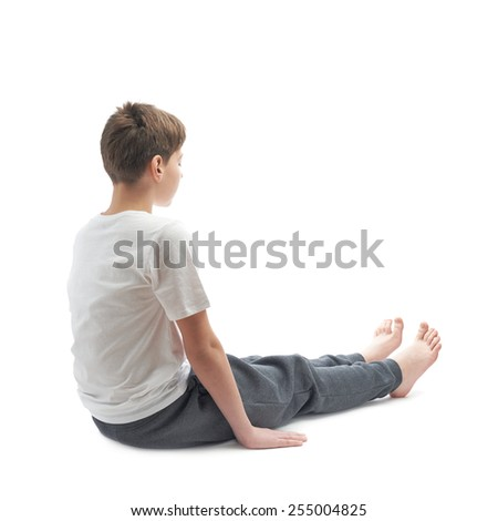 Caucasian 12 years old children boy in a white t-shirt stretching or doing yoga. Composition isolated over the white background
