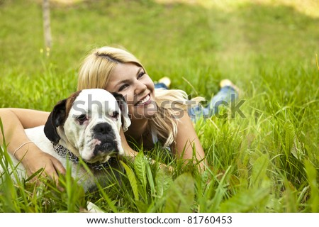 Caucasian young adult blond woman outdoor with boxer dog fall time - stock photo