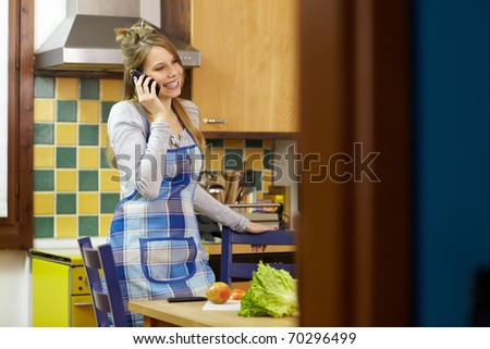 caucasian young adult woman cutting vegetables in kitchen while talking on the phone. Horizontal shape, side view, focus on background - stock photo