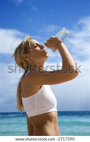 Caucasian young adult woman drinking water on beach. - stock photo