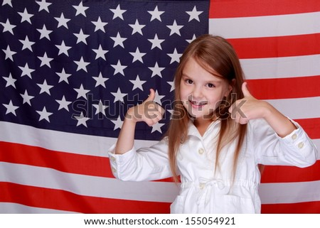 Caucasian young beautiful girl in a white jacket is standing on a of the American flag