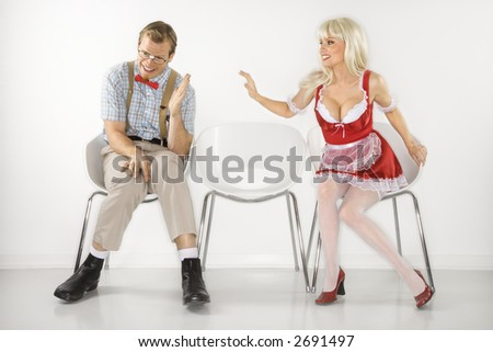 Caucasian young blonde woman sitting reaching over to shy Caucasian young man dressed like nerd. - stock photo