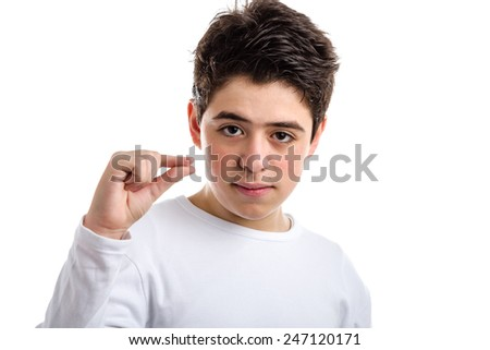 Caucasian young boy with acne in a white long sleeve t-shirt making pinching gesture with the thumb and index finger - stock photo