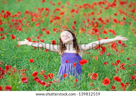 Caucasian young child feel the fresh air in flower field - stock photo