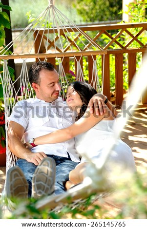 Caucasian young couple dressed in white on a rope hammock on the terrace of a country house lovingly looking rear view - stock photo