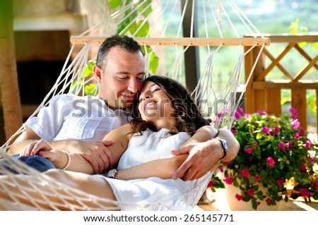 Caucasian young couple dressed in white on a rope hammock on the terrace of a country house lovingly looking - stock photo