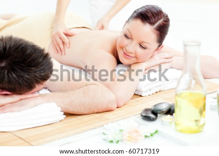 Caucasian young couple receiving a back massage in a spa center - stock photo
