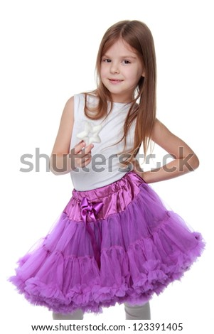 Caucasian young girl wearing white top and bright purple tutu skirt on white background