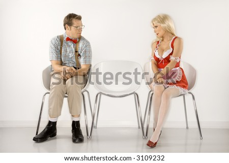 Caucasian young man dressed like nerd and Caucasian young blonde woman in french maid outfit sitting and looking at eachother. - stock photo
