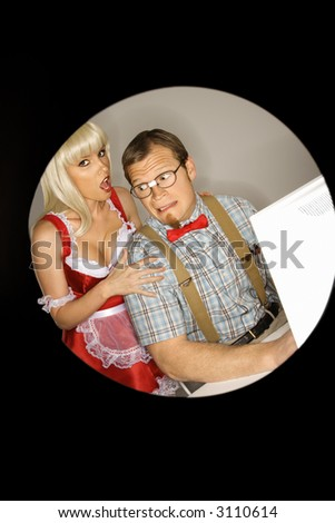 Caucasian young man dressed like nerd at computer looking back in fear at Caucasian blonde young woman dressed in french maid outfit. - stock photo