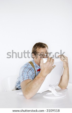 Caucasian young man dressed like nerd embracing computer with face pressed to monitor. - stock photo