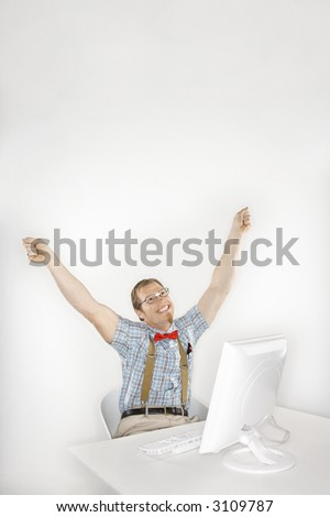 Caucasian young man dressed like nerd happy with arms raised in front of computer. - stock photo
