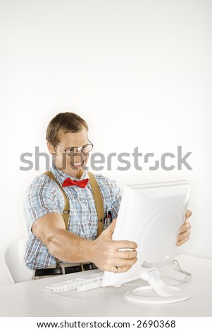 Caucasian young man dressed like nerd holding computer monitor in frustration. - stock photo