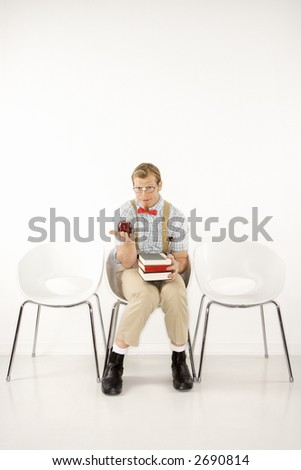 Caucasian young man dressed like nerd looking at viewer sitting with books and holding out apple. - stock photo