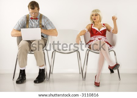 Caucasian young man dressed like nerd sitting with laptop with Caucasian young blonde woman looking at him. - stock photo