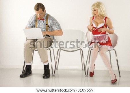 Caucasian young man dressed like nerd sitting with laptop with Caucasian young blonde woman trying to distract him with cleavage. - stock photo