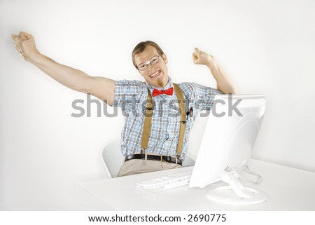 Caucasian young man dressed like nerd stretching arms out and happy in front of computer. - stock photo