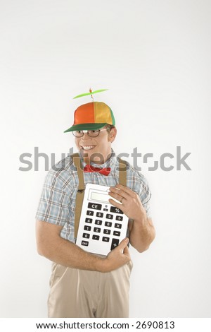Caucasian young man dressed like nerd wearing beanie and smiling while holding large calculator. - stock photo