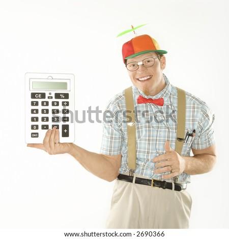 Caucasian young man dressed like nerd wearing beanie holding large calculator. - stock photo