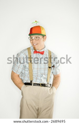 Caucasian young man dressed like nerd wearing propeller cap with hands in pockets.