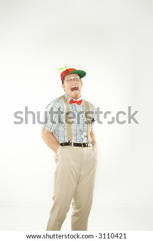 Caucasian young man dressed like nerd wearing propeller cap with hands in pockets looking at viewer with mouth open. - stock photo