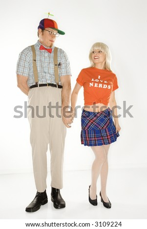 Caucasian young man dressed like nerd wearing propeller hat holding hands with Caucasian blonde young woman wearing tshirt reading I love nerds and plaid skirt. - stock photo