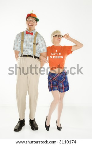Caucasian young man dressed like nerd wearing propeller hat with blonde Caucasian young woman in nerdy eyeglasses and tshirt reading I love nerds and plaid skirt. - stock photo
