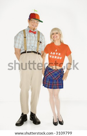 Caucasian young man dressed like nerd wearing propeller hat with Caucasian blonde young woman wearing tshirt reading I love nerds and plaid skirt. - stock photo