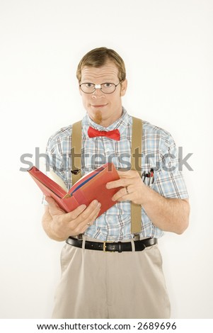 Caucasian young man dressed like nerd with book open looking at viewer. - stock photo
