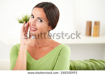 Caucasian young woman in green shirt looking at camera while smiling at home - copy space - stock photo