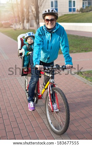 Caucasian young woman on a bicycle with little son behind  - stock photo