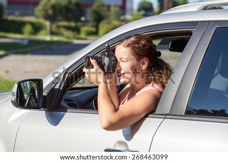 Caucasian young woman photographing while leaning out the window of car - stock photo
