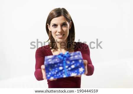 caucasian young woman showing present to the camera and smiling on white background