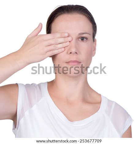 caucasian young woman use her hand to cover one eye while looking at the camera on white background, in studio - stock photo
