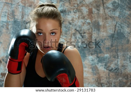Caucasian young woman wearing boxing gloves and throwing punch.