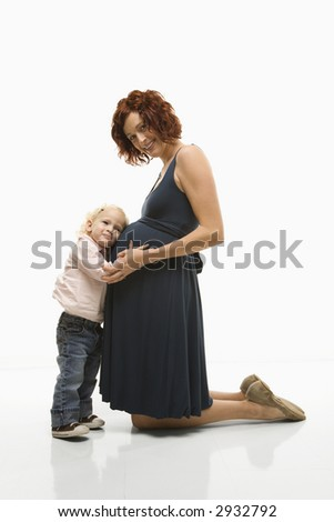Caucasion mid-adult attractive pregnant woman kneeling in front of female toddler who is pressing ear against belly.