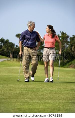 Caucasion mid-adult man and woman walking on golf course talking to each other. - stock photo