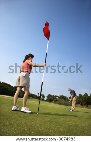 Caucasion mid-adult man putting golfball while Caucasion mid-adult woman holds flag. - stock photo