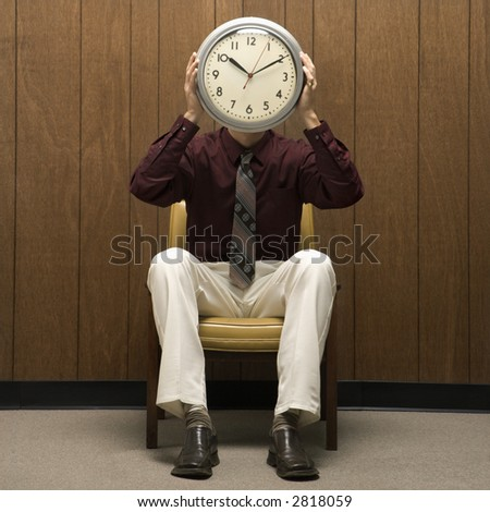Caucasion mid-adult retro businessman sitting in chair against wood paneling holding clock over face.