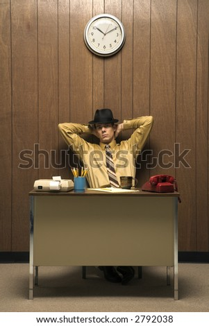 Caucasion mid-adult retro businessman wearing fedora sitting at desk leaning back with hands behind head. - stock photo